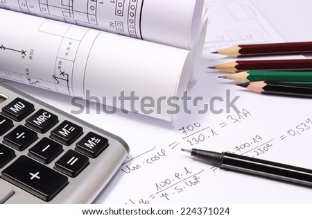 Rolled electrical diagrams, calculator, pencils and mathematical calculations for project,  drawings for the projects engineer jobs - stock photo