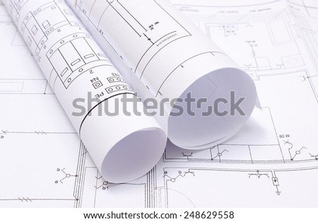 Rolled electrical diagrams lying on construction drawing of house, drawings for the projects engineer jobs - stock photo
