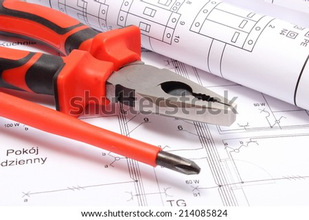 Rolled electrical diagrams with work tools lying on construction drawing of house, drawings for the projects engineer jobs