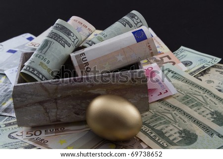Rolled Euro and Dollar currency with gold nest egg on global currencies to depict worldwide emphasis on funding retirements and social network benefits - stock photo