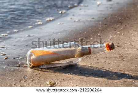 Rolled letter inside glass bottle on a beach  - stock photo