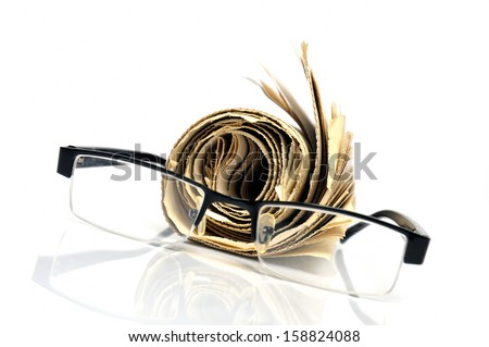 Rolled newspaper and black glasses - stock photo