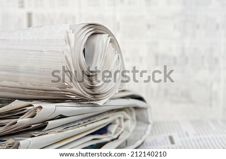 rolled newspaper on stack of newspapers against blurry background - stock photo