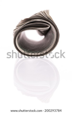 Rolled newspaper with Reflection on white background - stock photo
