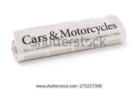 Rolled newspaper with the headline Cars and Motorcycles - stock photo