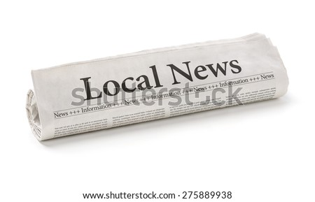 Rolled newspaper with the headline Local News - stock photo