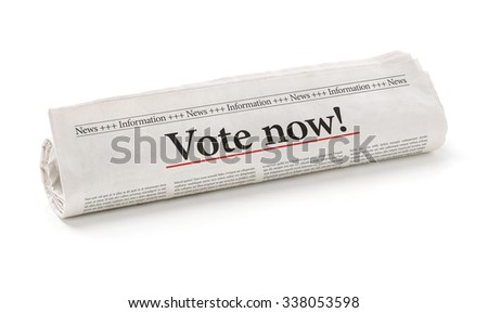 Rolled newspaper with the headline Vote now - stock photo