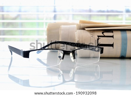 Rolled newspapers with glasses in front of a window - stock photo