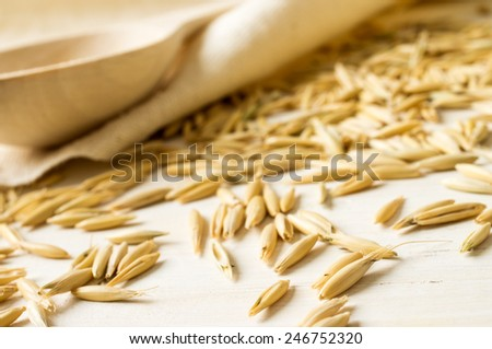 Rolled oats and oats in a wooden bowl - stock photo