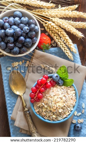 Rolled oats in a blue bowl on a napkin with spikes and spoon - stock photo