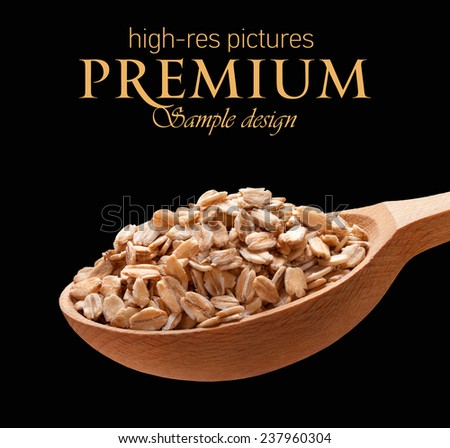 Rolled oats in a wooden spoon / cereal on wooden spoons isolated on black background with place for your text  - stock photo