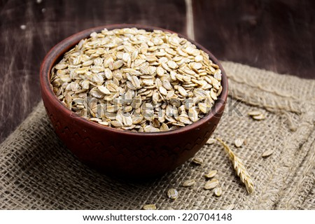 Rolled oats in brown bowl, close up food ingredients - stock photo