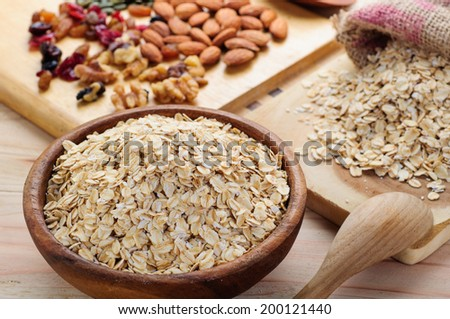 rolled oats in wooden bowl and muesli ingredients