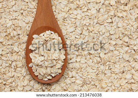 Rolled oats (oat flakes) in a wooden spoon on a rolled oats background. Closeup. - stock photo