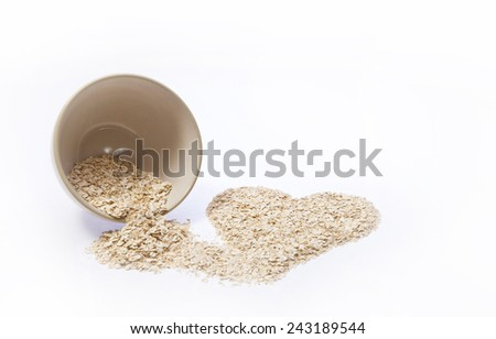 Rolled oats pouring out of a bowl into a heart shape  - stock photo