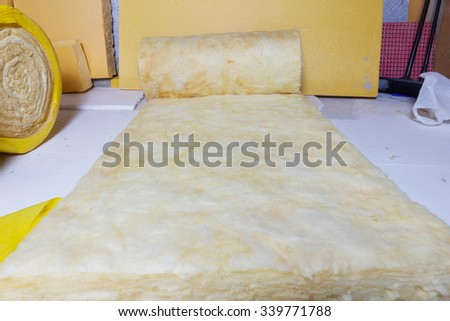 rolled out thermal insulation role in yellow package at attic background - stock photo