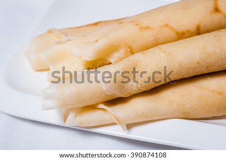 Rolled pancakes stuffed with cheese on a white plate.