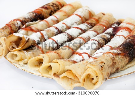 Rolled pancakes with powdered sugar and strawberry syrup. - stock photo