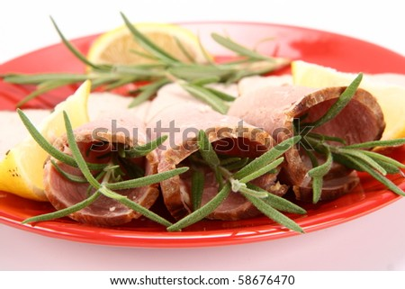 Rolled slices of ham filled with rosemary on a plate decorated with lemon - stock photo