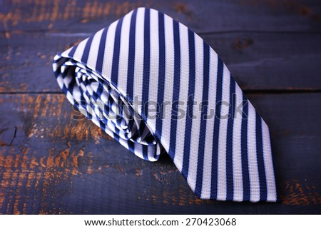 Rolled striped tie on wooden background