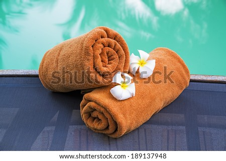 Rolled towels near the outdoor swimming pool  - stock photo