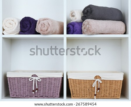 Rolled towels with wicker baskets on shelf of rack background - stock photo
