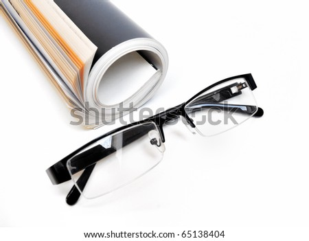 Rolled up black colored magazine and glasses over white background - stock photo