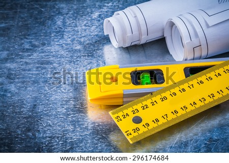 Rolled up blueprints ruler and construction level on metallic scratched background maintenance concept. - stock photo