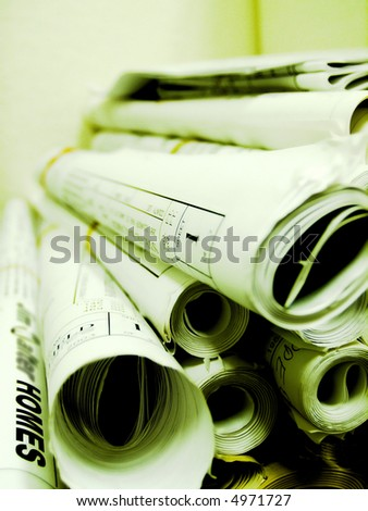 Rolled up blueprints (with green tint added for effect) - stock photo