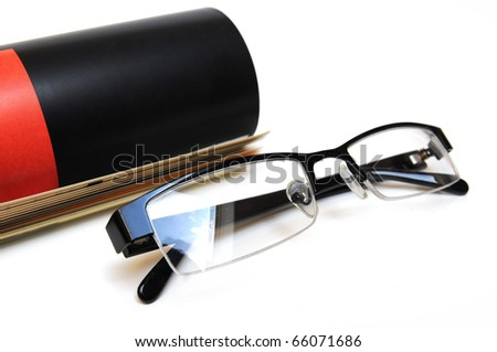 Rolled up magazine and black colored glasses over white background - stock photo