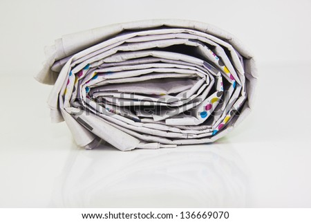 rolled up newspaper in closeup - stock photo