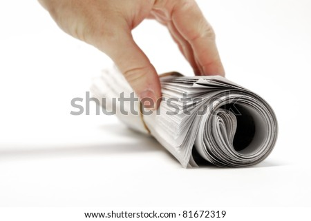 Rolled up newspaper isolated on white background with hand reaching - stock photo