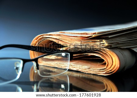 Rolled up newspaper with glasses - stock photo