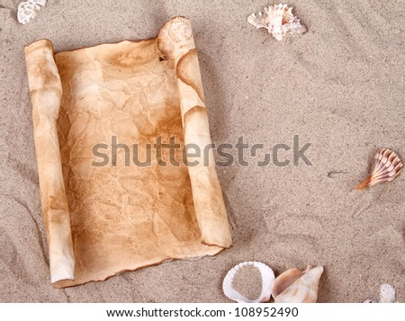 Rolled up old and weathered blank paper in the sand - stock photo