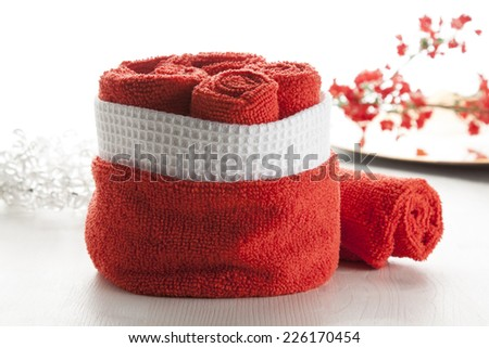 Rolled up red towels group on white background in bathroom. - stock photo