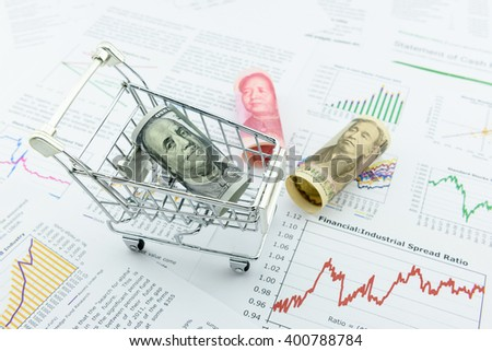 Rolled up scroll of US 100 dollar bill with image of Benjamin Franklin in a trolley and 2 notes of Chinese Yuan and Japanese Yen fall outside. A concept of money / currency trading between Asia and US - stock photo