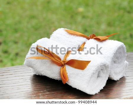 rolled up white spa towel on wooden table with green nature background - stock photo