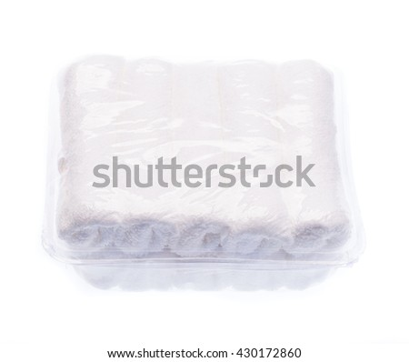 rolled up white towel inside package on white background - stock photo
