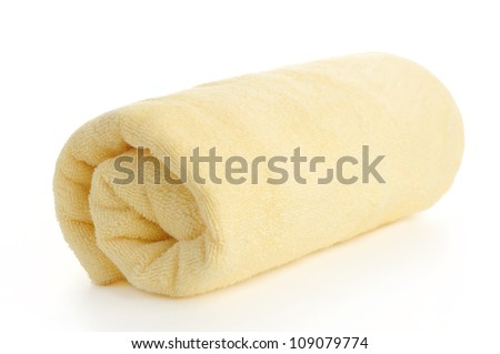 rolled up yellow beach towel on  white background - stock photo