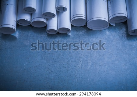 Rolled white blueprints on scratched metallic surface copy space image construction concept. - stock photo
