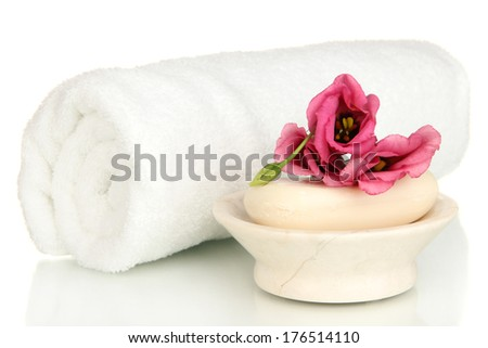 Rolled white towel, soap bar and beautiful flower isolated on white - stock photo