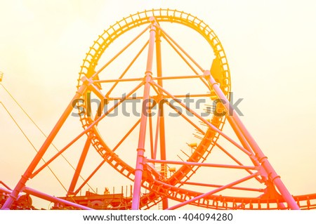 Roller Coaster in Theme Park by sunset - stock photo