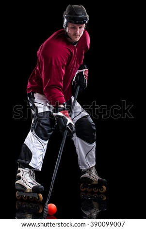 Roller hockey player. Studio shot over black.