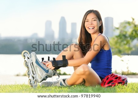 Roller skate girl skating. Young woman putting on skates going rollerblading in urban city park. Beautiful multiracial young woman smiling at camera with Montreal skyline in background. - stock photo