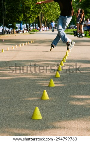 Roller skating young man training with inline rollerblades. - stock photo