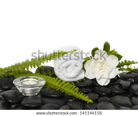 roller towel with green fern and gardenia flowers, candle on black stones - stock photo