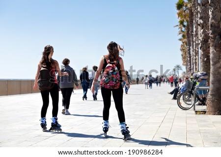 Rollerblading on the beach. Urban scene. - stock photo