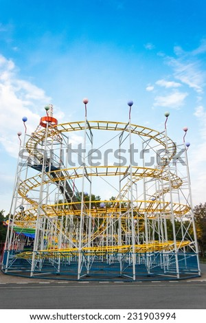 Rollercoaster in the evening against blue sky and white clouds. - stock photo