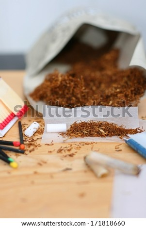 Rolling a cigarette, tobacco  (Nicotiana tabacum), rolling paper, filters and matches on a table, unhealthy life style. Focus on tobacco in the rolling paper - stock photo
