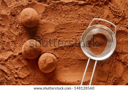 Rolling chocolate truffles in cocoa powder - stock photo